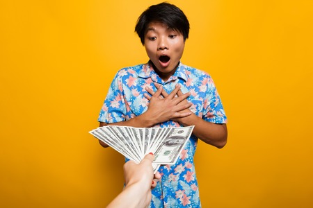 Amazed asian man receiving money banknotes isolated over yellow background 写真素材