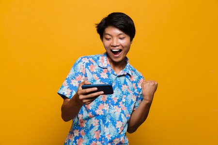 Image of an excited young asian man standing isolated over yellow background play games by mobile phone make winner gesture.