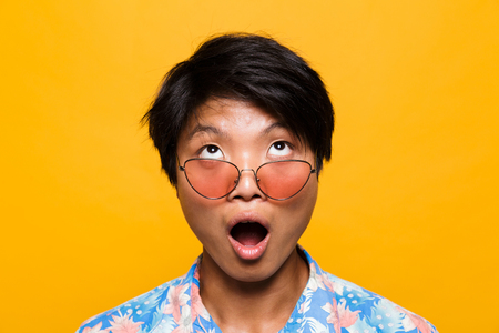 Close up portrait of a shocked asian man in sunglasses isolated over yellow background, looking up