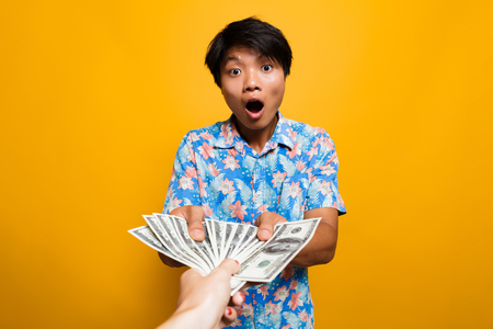 Astoinished asian man receiving money banknotes isolated over yellow background Stock Photo