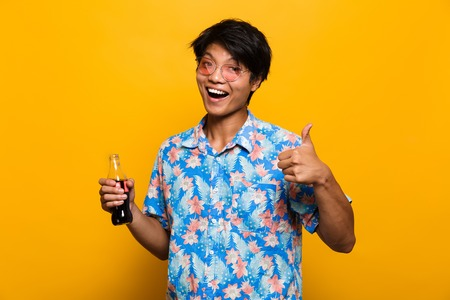 Portrait of a happy asian man isolated over yellow background, holding bottle with fizzy drink, showing thumbs up