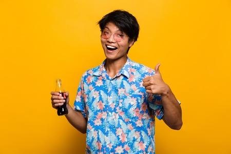 Retrato de un hombre asiático feliz aislado sobre fondo amarillo, sosteniendo una botella con bebida gaseosa, mostrando los pulgares para arriba