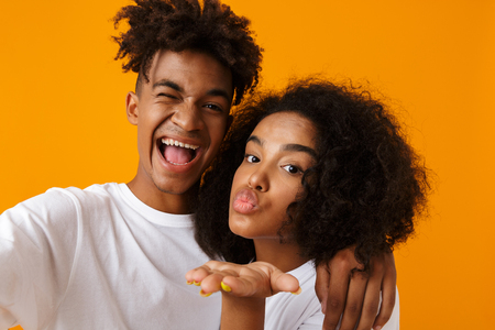 Image of happy young cute african couple posing isolated over beige background blowing kisses take a selfie by camera.