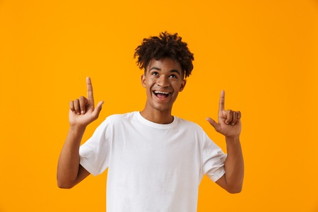 Cheerful young african man in t-shirt standing isolated over yellow background, pointing fingers up