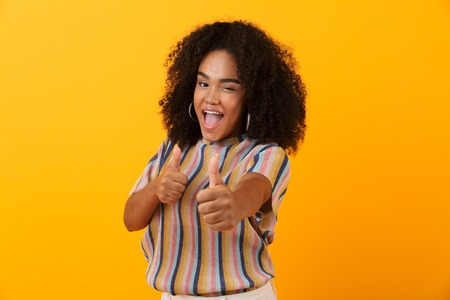 Image of happy young african cute girl posing isolated over yellow background make thumbs up gesture.