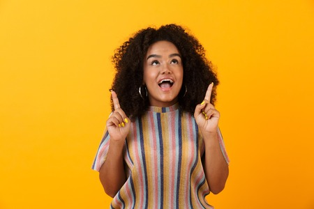 Image of happy young african cute girl posing isolated over yellow background pointing to copyspace.