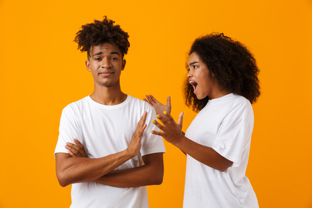 Portrait of an african couple standing isolated over yellow background, having an argument, shouting Stock Photo