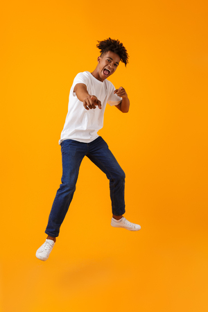 Image of happy young african man jumping isolated over yellow background pointing to you. Stok Fotoğraf
