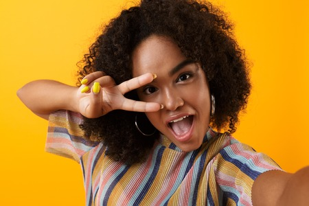 Image of beautiful young happy african cute girl posing isolated over yellow background take a selfie with peace gesture.