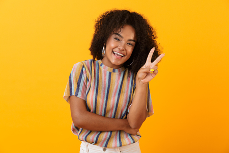 Image of happy young african cute girl posing isolated over yellow background make peace gesture. Banco de Imagens - 110978294