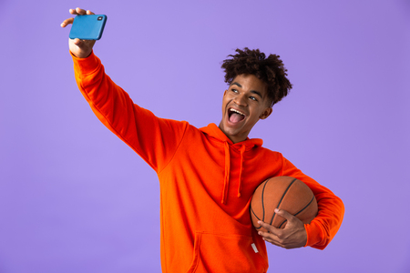Portrait of a cheerful young african man holding a basketball isolated over violet background, takign a selfie Standard-Bild - 110978302