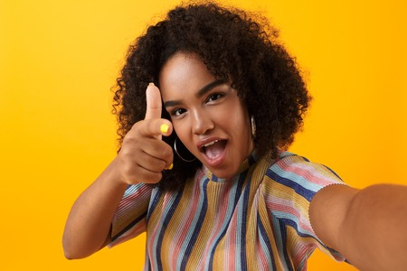 Image of beautiful young happy african cute girl posing isolated over yellow background take a selfie pointing.