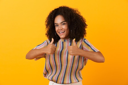 Image of happy young african cute girl posing isolated over yellow background make thumbs up gesture. Banco de Imagens - 110978359