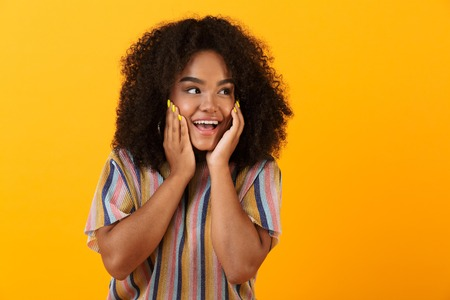 Image of happy young african cute girl posing isolated over yellow background looking aside.
