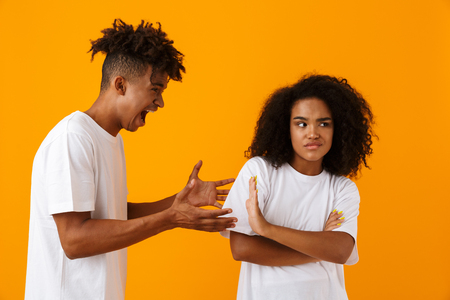 Portrait of an angry african couple standing isolated over yellow background, having an argument, shouting