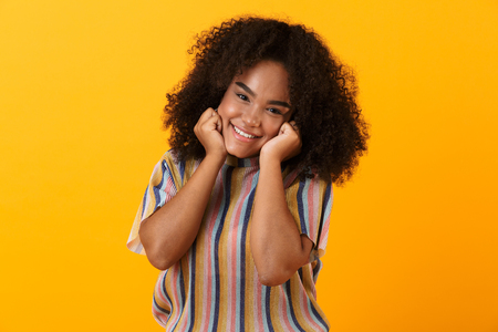 Image of happy young african cute girl posing isolated over yellow background. Banco de Imagens - 110978470