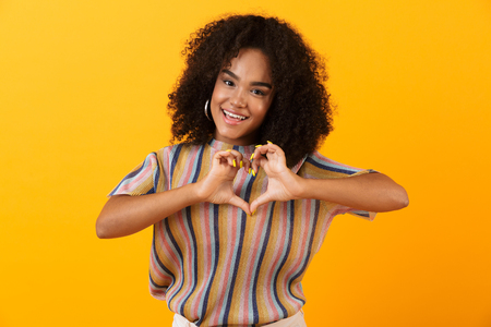 Image of happy young african cute girl posing isolated over yellow background showing heart love gesture.
