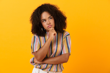 Image of thoughtful young african cute girl posing isolated over yellow background. Banco de Imagens - 111514032