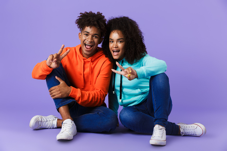 Image of happy young cute african couple posing isolated over violet background showing peace gesture.