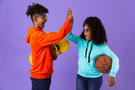 Cheerful young african couple standing isolated over violet background, giving high five, holding skateboard and basketball