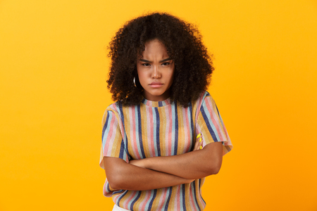 Image of displeased young african cute girl posing isolated over yellow background. Banco de Imagens - 110978656