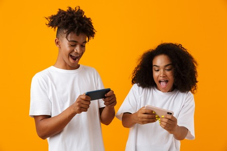 Image of excited young cute african couple isolated over yellow background play games by mobile phones. Stock Photo