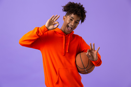 Portrait of a cheerful young african man holding a basketball isolated over violet background, showing ok sign