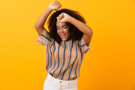 Image of happy young african cute girl posing isolated over yellow background dancing. Banco de Imagens