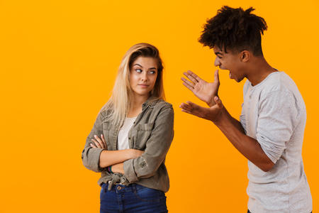 Portrait of a multiethnic couple standing isolated over yellow background, having an argument