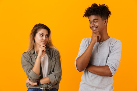 Portrait of a pensive multiethnic couple standing isolated over yellow background, looking at each other