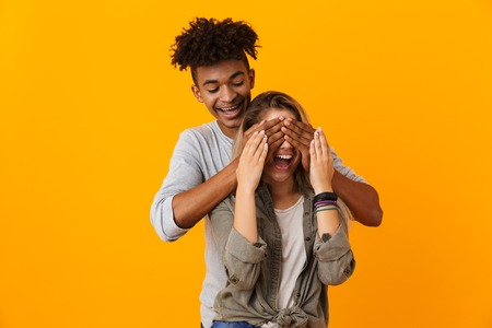Portrait of a smiling multiethnic couple standing isolated over yellow background, covering eyes of his girlfriend
