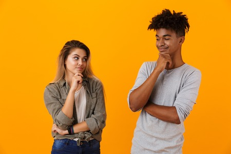 Portrait of a smiling pensive multiethnic couple standing isolated over yellow background, looking at each other Stock Photo