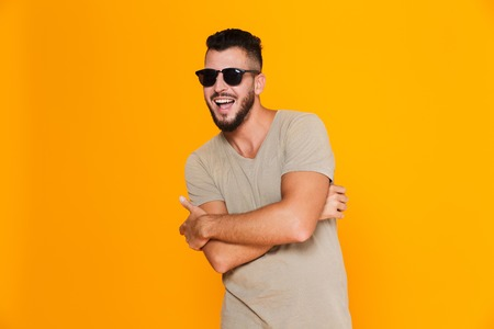 Portrait of a cheerful young casual man in sunglasses standing isolated over orange background, posing Stok Fotoğraf