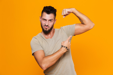 Portrait of a happy young casual man standing isolated over orange background, pointing at his bicep Banque d'images - 110979137