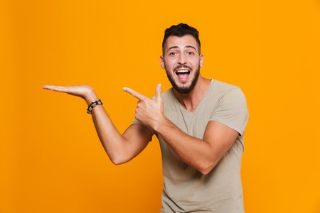 Image of emotional young happy man posing isolated over yellow background pointing. Stok Fotoğraf
