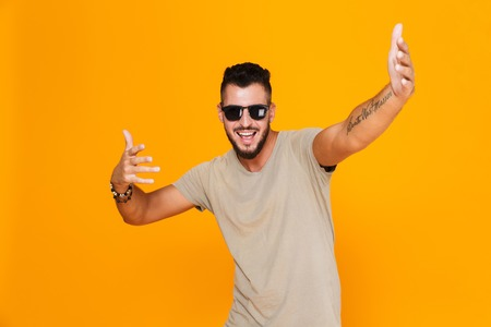 Portrait of a cheerful young casual man in sunglasses standing isolated over orange background, posing with outstetched hands