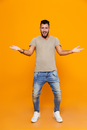 Full length portrait of a confused young casual man standing isolated over orange background, shrugging shoulders 스톡 콘텐츠