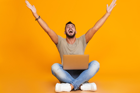 Portrait of a happy young casual man sitting isolated over orange background, holding laptop computer on his lap, celebrating success
