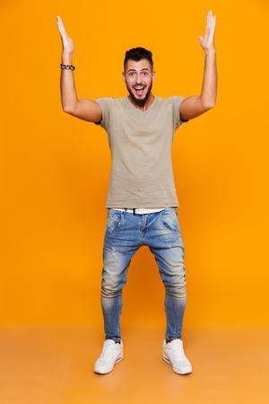 Full length portrait of a cheerful young casual man standing isolated over orange background, holding hands up