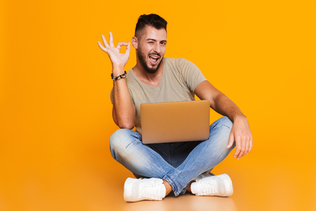 Portrait of a happy young casual man sitting isolated over orange background, holding laptop computer on his lap, showing ok, winking Stok Fotoğraf