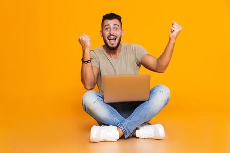 Portrait of a happy young casual man sitting isolated over orange background, holding laptop computer on his lap, celebrating