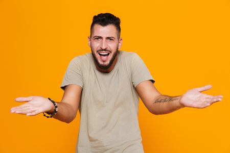 Portrait of a confused young casual man standing isolated over orange background, shrugging shoulders Stock Photo