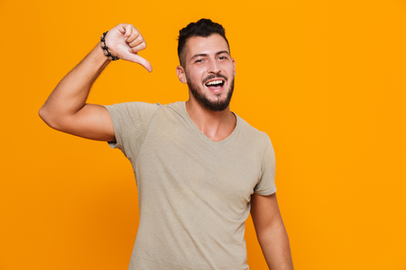 Portrait of a happy young casual man standing isolated over orange background, pointing at himself Banque d'images - 110979283