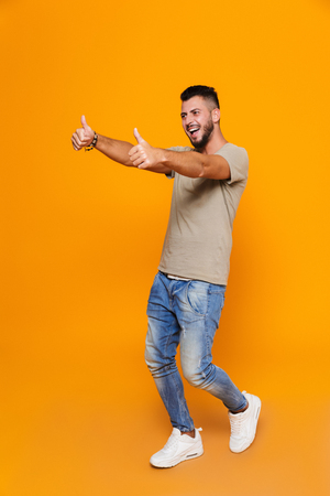 Full length portrait of a smiling young casual man standing isolated over orange background, showing two thumbs up away