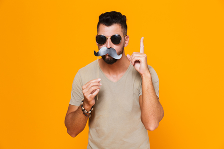 Portrait of a cheerful young casual man in sunglasses standing isolated over orange background, grimacing with pretended moustaches