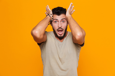 Image of shocked excited young man posing isolated over yellow background.