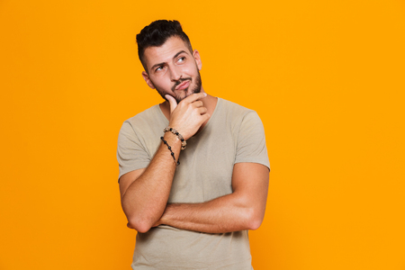 Portrait of a pensive young casual man standing isolated over orange background, looking away