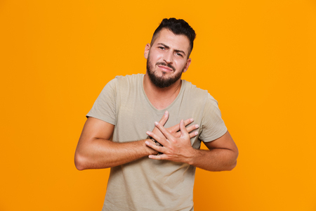 Portrait of a young casual man standing isolated over orange background, having a heart attack