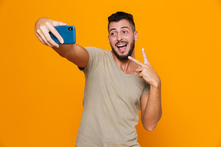 Portrait of an excited young bearded man in t-shirt isolated over orange background, holding mobile phone, taking a selfie, showing peace gesture