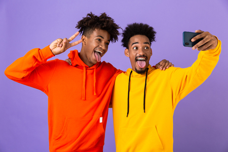 Two funny african man friends dressed in colorful hoodies standing isolated over violet background, taking a selfie Stock Photo